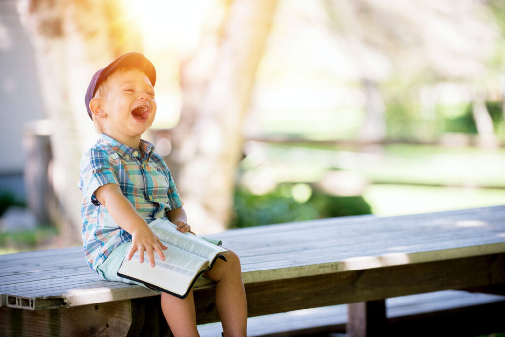 Picture of laughing Child sitting on bench with book