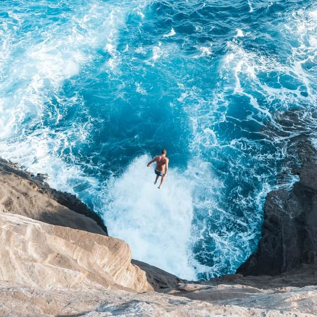 Picture of man jumping off of Hawaii Cave - About Guidebyday
